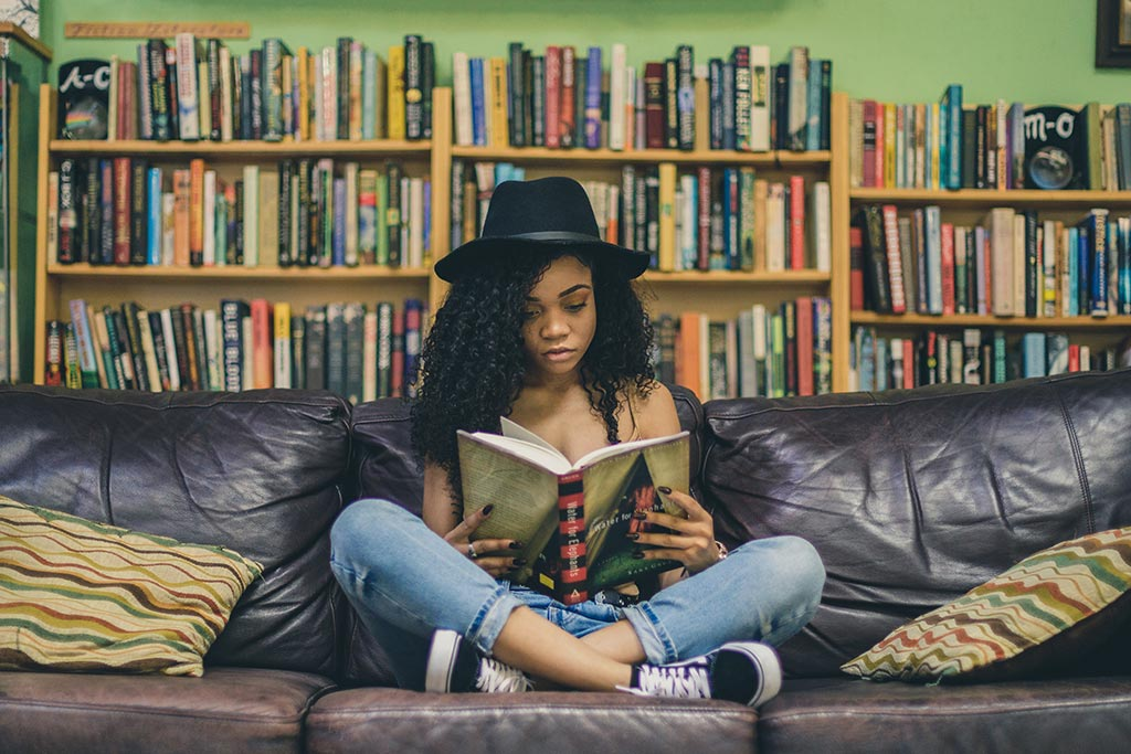 Girl reading on couch Photo taken by Seven Shooter on Unsplash